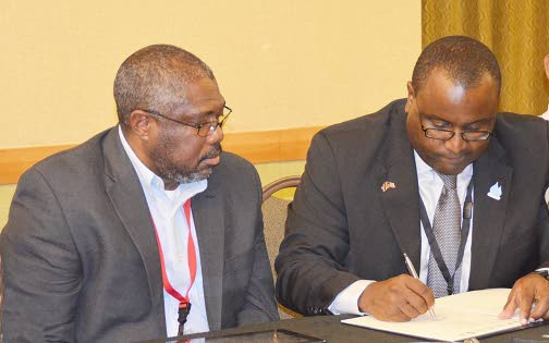 Dr David Farell, principal of the the Caribbean Institute for Meteorology and Hydrology, looks on while outgoing Caribbean Water and Waste Water Association President Jason Johnson signs the climate change agreement.